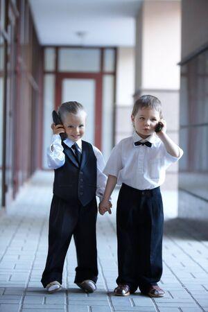 ni�os hablando: Los ni�os en los negocios se adapten con tel�fono m�vil al aire libre. Concepto.