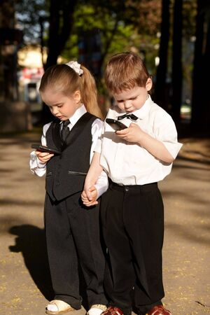Children in business suit with mobile phone outdoors. Concept. Stock Photo - 6964138