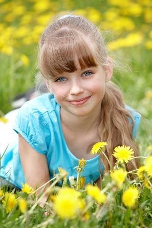 only: Little girl lying on grass in flower. Outdoor. Stock Photo