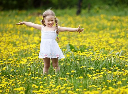 flowers field: Little girl  on grass in flower. Outdoor. Stock Photo