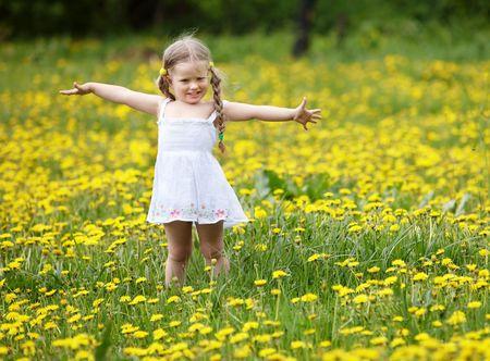 campo de flores: Niña sobre césped en flor. Al aire libre. Foto de archivo