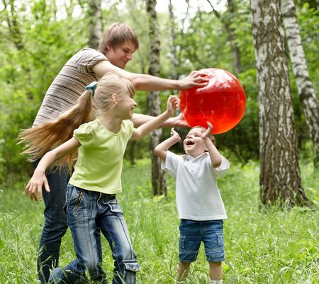 upbringing: Outdoor happy family with children plaing ball  on green grass.