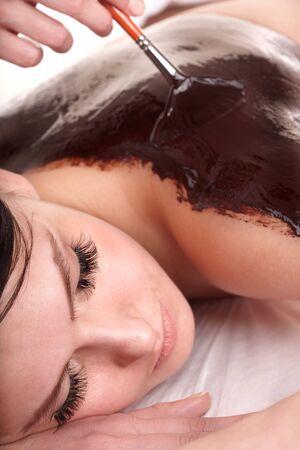 Girl having chocolate body mask apply by beautician. photo