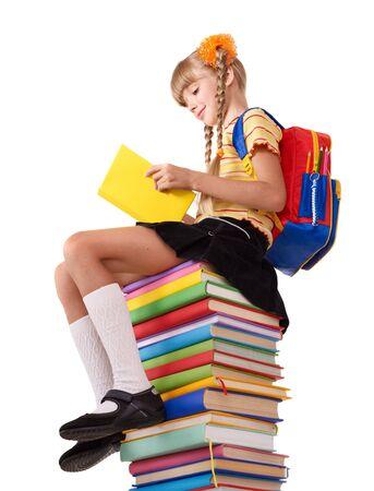 Schoolgirl sitting on pile of books. Isolated. photo