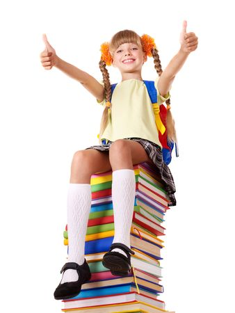 Girl sitting on pile of books showing thumbs up. Isolated. photo