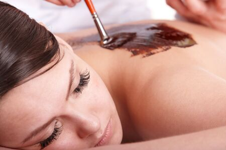 beauty parlour: Girl having chocolate body  mask in  beauty parlour.