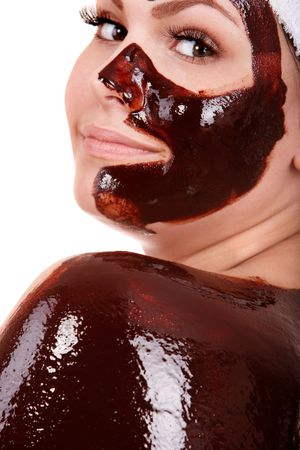 beauty parlour: Beautiful young woman having  chocolate facial mask. Isolated.