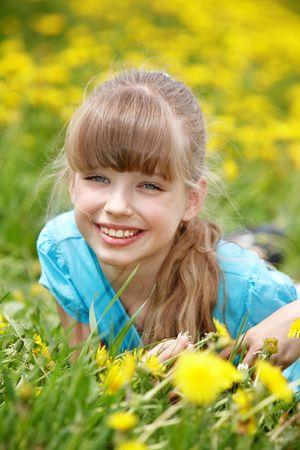 Little girl lying on grass in flower. Outdoor. photo