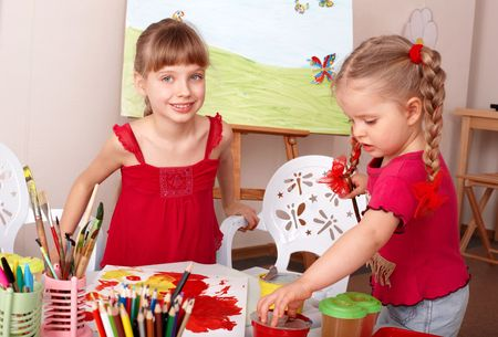 school activities: Children painting colour paints in preschool. Stock Photo