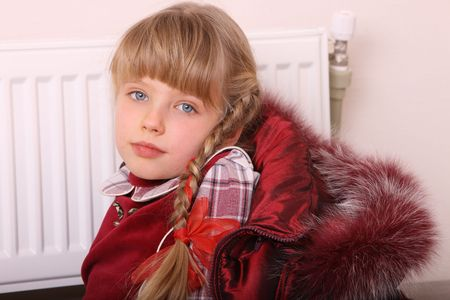 Girl in coat warm  near radiator.  Energy crisis. photo