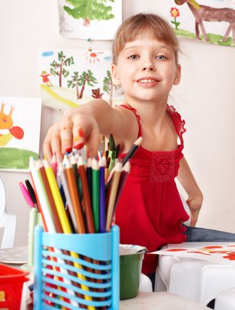 upbringing: Child drawing colour pencil in preschool. Childcare