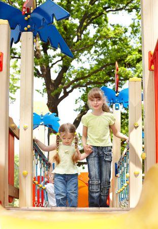 Children on slide outdoor in park. Happy childhood. photo