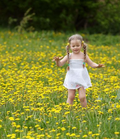 florecitas: Niña sobre césped en flor. Al aire libre.