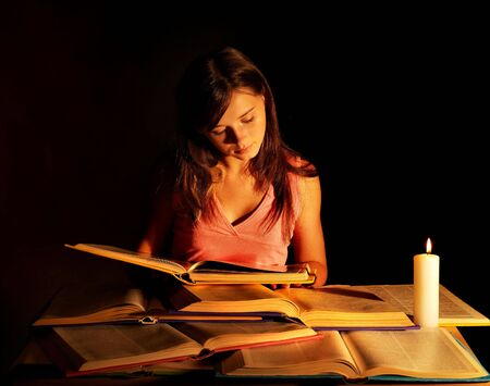 Girl reading open book on table. Black background. photo