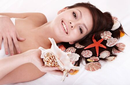 Beauty young woman holding starfish.  Spa resort. photo