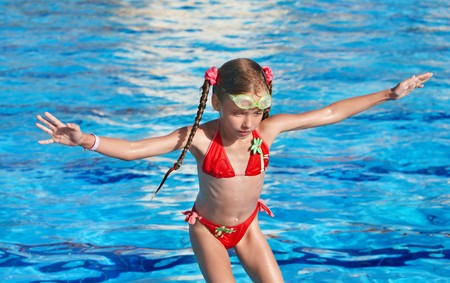 Girl with protective goggles and red swimsuit jump in swimming pool photo