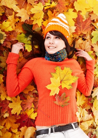 Young woman in autumn orange leaves. Outdoor. Stock Photo - 7778745