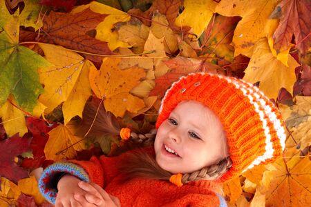 Little girl in autumn orange  leaves. Outdoor. photo