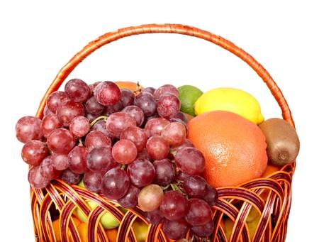 Group of fresh fruit in basket. Isolated. photo