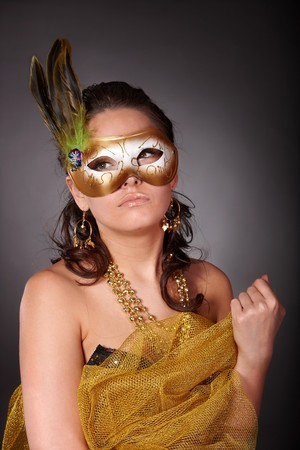 Beautiful young woman in gold mask on grey background. photo