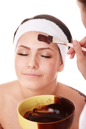 Girl having chocolate facial mask apply by beautician. photo