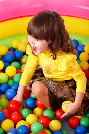 Happy little girl in group colourful ball. Stock Photo - 7779427
