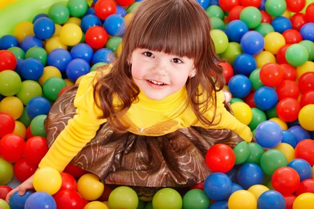 child birthday: Happy little girl in group colourful ball.