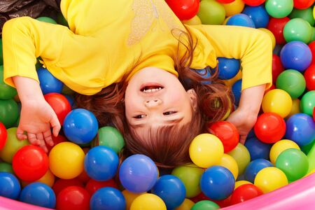 Happy little girl in group colourful ball. Stock Photo - 7779728