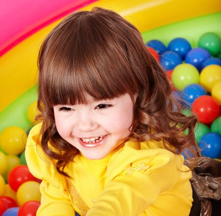 Happy little girl in group colourful ball. Stock Photo - 7779350