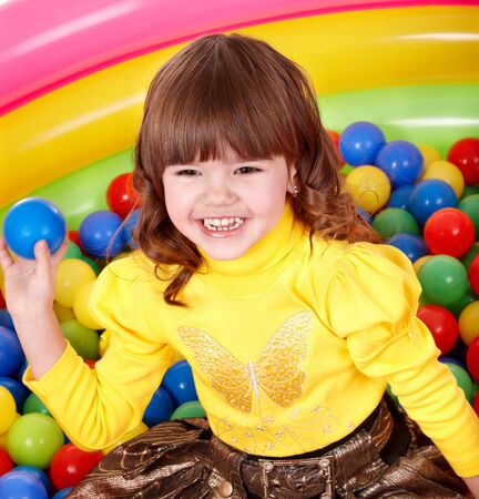 Little girl  in group colourful ball. photo