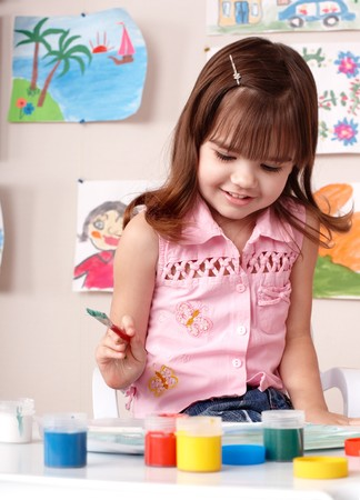 Child preschooler painting in classroom. Child care. photo