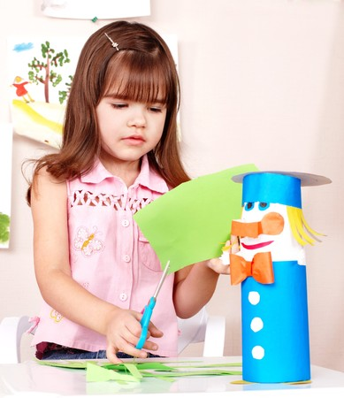 paper cutting: Serious child cutting paper by scissors.