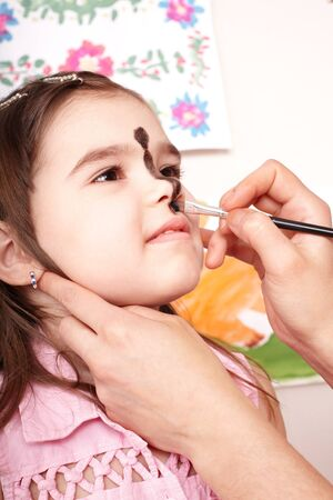 Little girl with  face painting in play room. Make up. photo