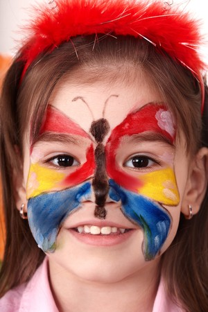 Little girl  making face painting. photo