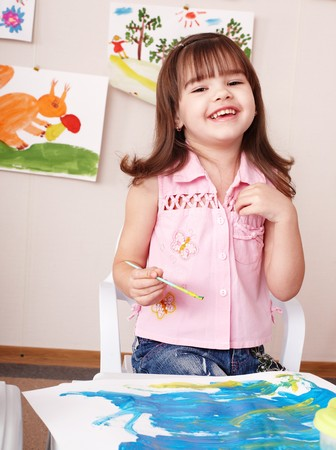 Child painting picture  in play room. Preschool. photo