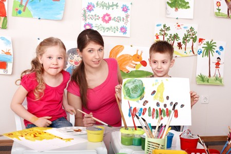 Children painting with teacher in art class. Child care. Stock Photo - 7810768
