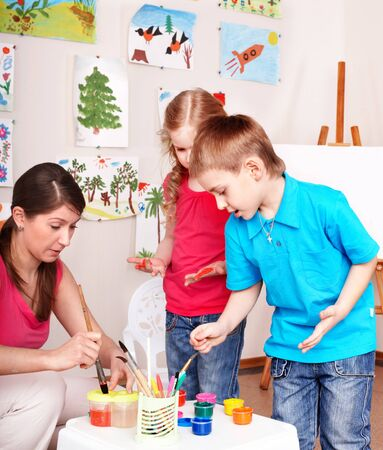 Children painting with teacher in play room. photo