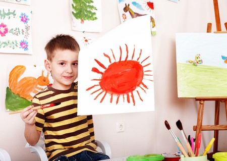 child care: Child with picture and brush in play room. Preschool.