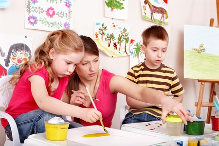 upbringing: Children painting with teacher. Child development.