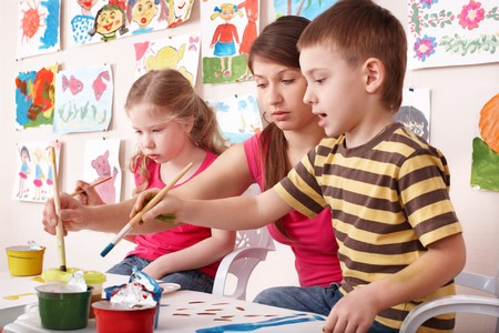 Children painting with teacher in art class. Child care. photo