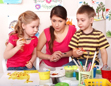 Children with teacher painting  paints in play room. Child care. Stock Photo - 8332974