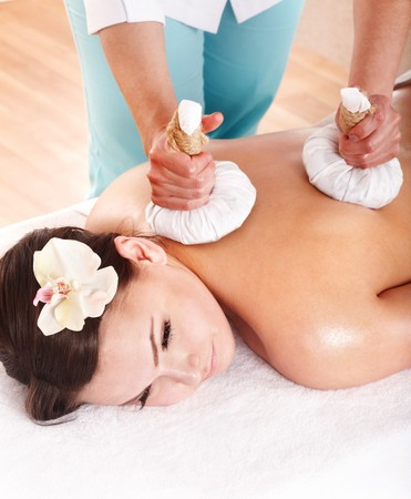 aroma therapy: Young woman  having Thai herb compress massage  in beauty spa.