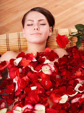 bathtubs: Beautiful young woman in rose petal swim water. Beauty spa.