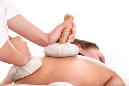 beauty therapist: Girl  having Thai herb compress massage in beauty spa. Body care.