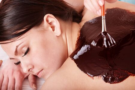 Beautiful girl having chocolate facial mask apply by beautician. photo