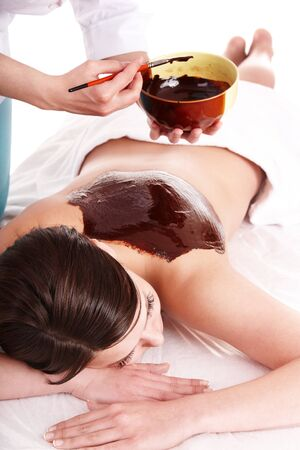 Young woman having chocolate body mask. photo