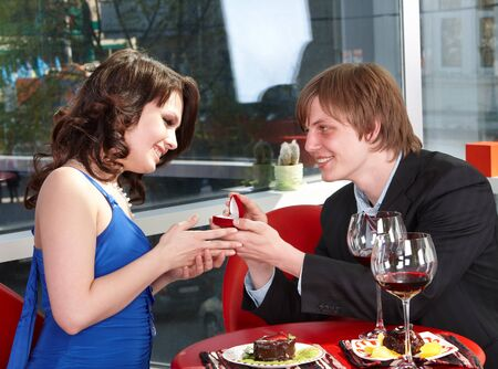 propose: Man propose marriage to girl in restaurant.