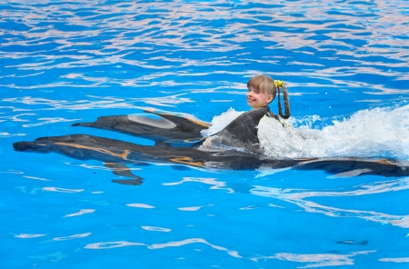 dolphins: Happy child and dolphin swimming in blue water. Stock Photo