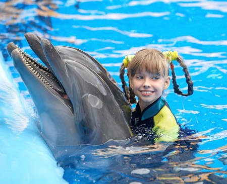 Happy child and dolphin in blue water. photo