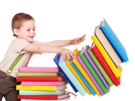 able: Little boy reading pile of books.